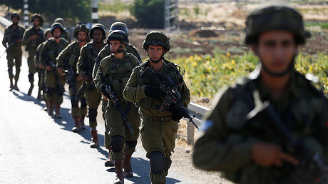 Israeli soldiers provide security during a protest against the killing of two settlers by Palestinians in two separate attacks, near the Jewish settlement of Otniel in the West Bank, July 10, 2016. © Baz Ratner