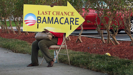 Woman holding an Obama Care sign in front of a medical center in Miami. File photo. © 