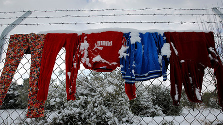 Clothes that belong to stranded refugees are covered with snow as they hang on a fence during a show storm at a refugee camp north of Athens, Greece January 10, 2017. © Yannis Behrakis