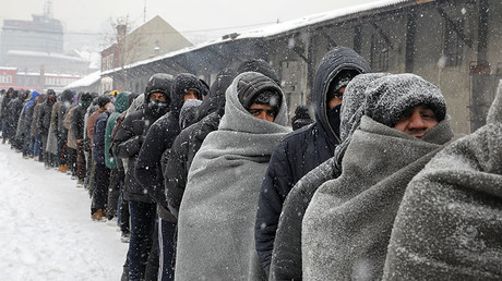 Migrants wait in line to receive a plate of free food during a snowfall outside a derelict customs warehouse in Belgrade, Serbia, January 11, 2017. © Marko Djurica