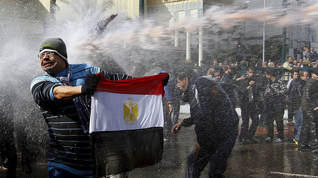 FILE PHOTO: A protester holds an Egyptian flag as he stands in front of water canons during clashes in Cairo January 28, 2011. © Yannis Behrakis