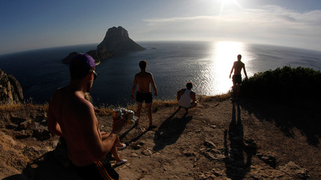 Tourists meet to watch the sunset at Es Vedra cliffs, on the Spanish Balearic island of Ibiza © Enrique Calvo