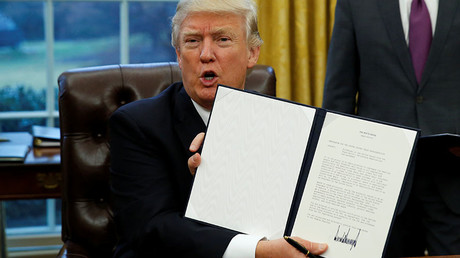 U.S. President Donald Trump holds up the executive order on withdrawal from the Trans Pacific Partnership after signing it in the Oval Office of the White House in Washington January 23, 2017. ©Kevin Lamarque