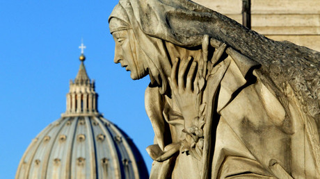 Saint Peter's Basilica is seen behind a statue depicting Saint Catherine. Rome, Italy © Alessia Pierdomenico