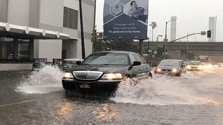 Cars drive through rain on a flooded street in Los Angeles, California, U.S., January 22, 2017. © Lucy Nicholson