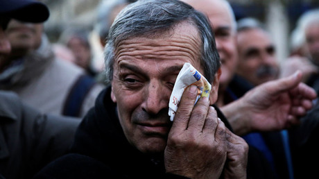 A Greek pensioner wipes his face with a fake euro banknote during a demonstration against government policies affecting pensioners in Athens © Alkis Konstantinidis
