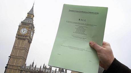 A journalist poses with a copy of the Brexit Article 50 bill, introduced by the government to seek parliamentary approval to start the process of leaving the European Union, in front of the Houses of Parliament in London, Britain, January 26, 2017. © Toby Melville