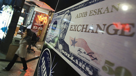 A woman walks past a currency exchange shop at a shopping centre in northern Tehran, Iran. © Morteza Nikoubazl
