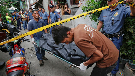 FILE PHOTO A body is taken out of a house where two men were killed during a drugs related police operation in Manila, Philippines © Damir Sagolj