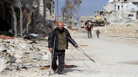 A man on crutches walks through a damaged neighbourhood in Aleppo, Syria January 30, 2017. ©Ali Hashisho