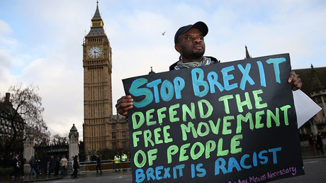 A demonstrators holds an anti-Brexit placard reading