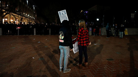 Two demonstrators hold signs as they face a police line after a student protest turned violent at UC Berkeley © Stephen Lam