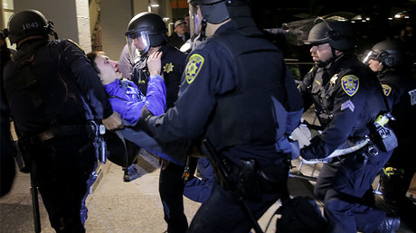A protester is carried by police officers during a protest on the UC Berkeley campus, February 1, 2017. © Elijah Nouvelage / Getty Images