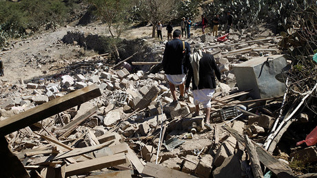 People walk on the rubble of a house destroyed by a Saudi-led air strike in Sanaa, Yemen. ©Mohamed al-Sayaghi