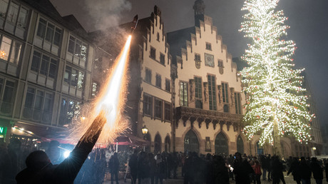 A man sets off a firecracker from his hand on the Roemerberg in Frankfurt, Germany, 31 December 2016. © Boris Roessler