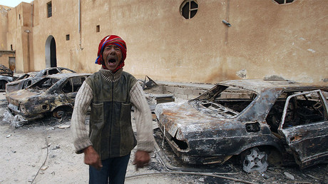 FILE PHOTO: A man gestures in front of burnt vehicles in a state security building in Tobruk, east of Libya. © Suhaib Salem