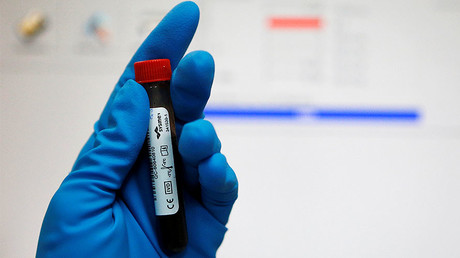 FILE PHOTO: A technician holds a test tube with a blood sample at the Russian anti-doping laboratory. © Sergei Karpukhin