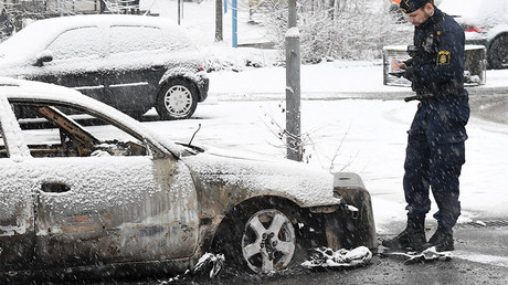 A policeman investigates a burnt car in Rinkeby suburb, outside Stockholm, Sweden February 21, 2017. © TT News Agency / Fredrik Sandberg