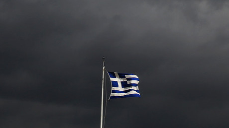 A Greek flag flutters atop the Acropolis hill in Athens © Yannis Behrakis