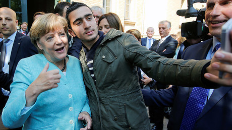 FILE PHOTO: Syrian refugee Anas Modamani takes a selfie with German Chancellor Angela Merkel © Fabrizio Bensch