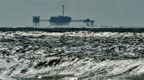 An oil and gas drilling platform stands offshore as waves churned from Tropical Storm Karen come ashore in Dauphin Island, Alabama © Steve Nesius