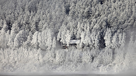 A wooden house is seen through fog in the snow-covered Taiga forest © Ilya Naymushin