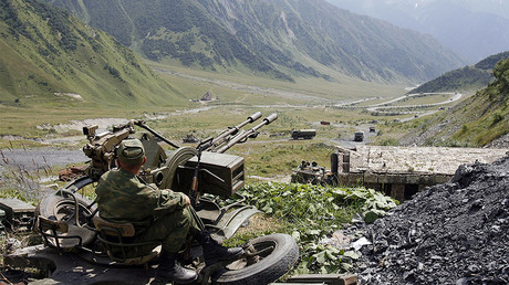 FILE PHOTO: A Russian soldier mans a gun as military vehicles approach the  border with South Ossetia © Denis Sinyakov