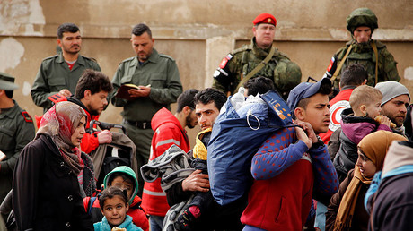 Syrian army soldiers (back L) and Russian soldiers (back R) monitor as rebel fighters and their families evacuate the besieged Waer district in the central Syrian city of Homs, March 18, 2017. © Omar Sanadiki