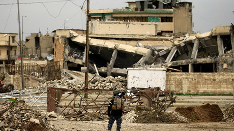 A federal policeman carries his weapon as he stands near buildings destroyed in clashes during a battle against Islamic State militants, in Mosul, Iraq March 19, 2017. © Thaier Al-Sudani
