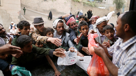 People gather to collect food rations at a food distribution center in Sanaa, Yemen © Khaled Abdullah / Reuters