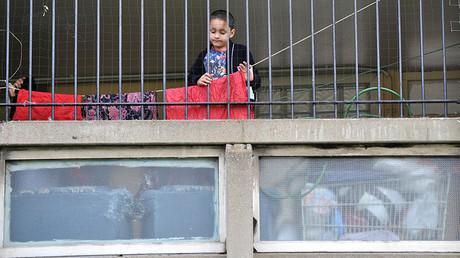 A child plays behind railings on the Robin Hood Gardens estate in Poplar, in East London © Jas Lehal