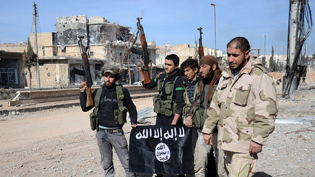FILE PHOTO. Rebel fighters, part of the Turkey-backed Euphrates Shield alliance, pose with an Islamic State group flag. © AFP