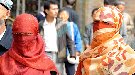 Uighur women wearing face veils walk on a street in Urumqi © Stringer