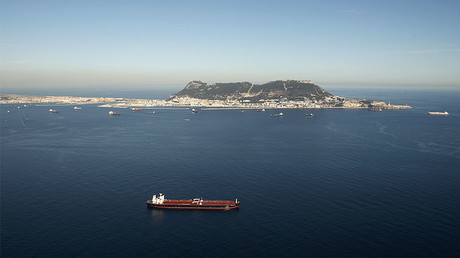 A merchant marine ship sails past the Rock of Gibraltar in the Strait of Gibraltar. © Jon Nazca