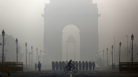 A man rides his bicycle next to Indian soldiers marching in front of India Gate on a smoggy morning in New Delhi, India © Anindito Mukherjee