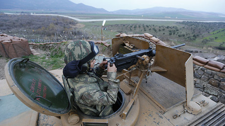 A Turkish soldier on an armoured military vehicle surveys the border line between Turkey and Syria. ©Murad Sezer