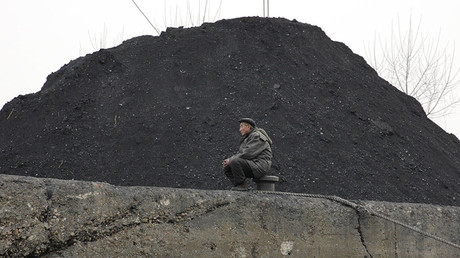A North Korean man sits beside a pile of coal on the bank of the Yalu River in the North Korean town of Sinuiju. © Adam Dean