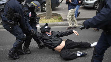 Riot police officers detain a man during a demonstration called