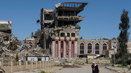 A woman walks in front of the remains of the University of Mosul, which was burned and destroyed during a battle with Islamic State militants, in Mosul © Marko Djurica