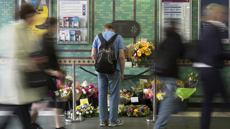 FILE PHOTO: A man looks at floral tributes for victims of the July 7, 2005 London bombings. © Neil Hall