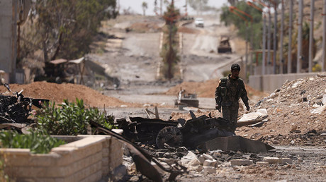 A Syrian Democratic Forces (SDF) fighter walks through a damaged street in the town of Tabqa, in Raqqa, Syria May 12, 2017 © Rodi Said