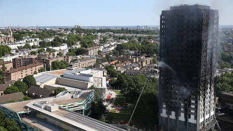 A firefighter hoses down Grenfell Tower in North Kensington, west London © Neil Hall