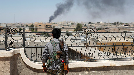 FILE PHOTO: A Kurdish fighter from the People's Protection Units (YPG) looks at a smoke after an coalition airstrike in Raqqa, Syria. © Goran Tomasevic