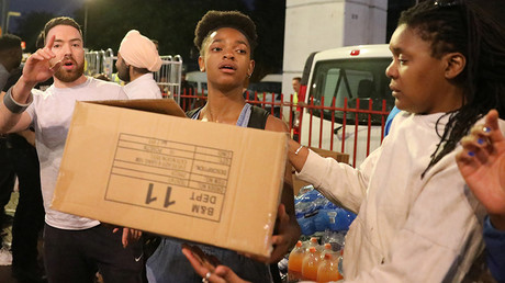 People distribute boxes of food near the scene of the fire which destroyed the Grenfell Tower block, June 15, 2017. © Paul Hackett