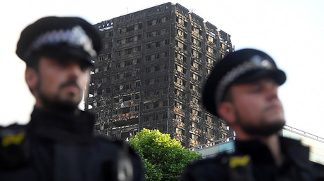 Police officers stand in front of the The Grenfell Tower block, north Kensington, West London, Britain. © Toby Melville