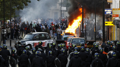 FILE PHOTO Police officers in riot gear block a road near a burning car on a street in Hackney, east London August 8, 2011.© Luke MacGregor