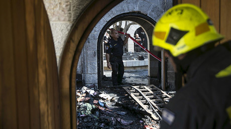 An Israeli police officer surveys the scene of a fire at the Church of Loaves and Fishes on the shores of the Sea of Galilee in northern Israel June 18, 2015. ©Baz Ratner