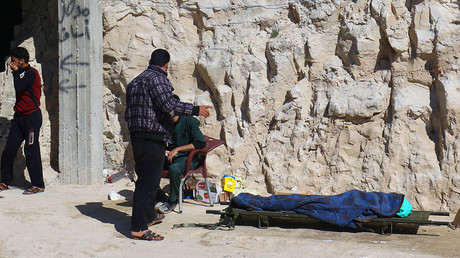 People stand near a dead body, described by rescue workers as a suspected gas attack victim in the town of Khan Shaykhun in Idlib, Syria April 4, 2017. © Ammar Abdullah