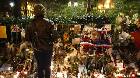 A woman looks at flowers, candles and messages in tribute to victims near the Bataclan concert hall in Paris, France, November 20, 2015. ©Charles Platiau