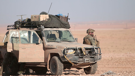 FILE PHOTO: A U.S. fighter stands near a military vehicle, north of Raqqa city, Syria. ©Rodi Said